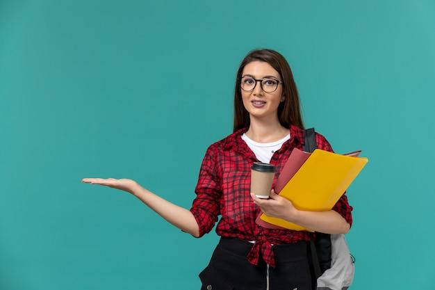 Vue de face de l'étudiante portant sac à dos tenant des fichiers et du café sur le mur bleu