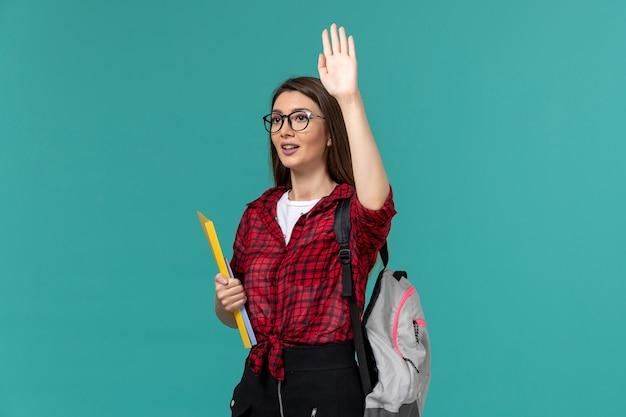 Vue de face de l'étudiante portant sac à dos et tenant des fichiers levant la main sur le mur bleu