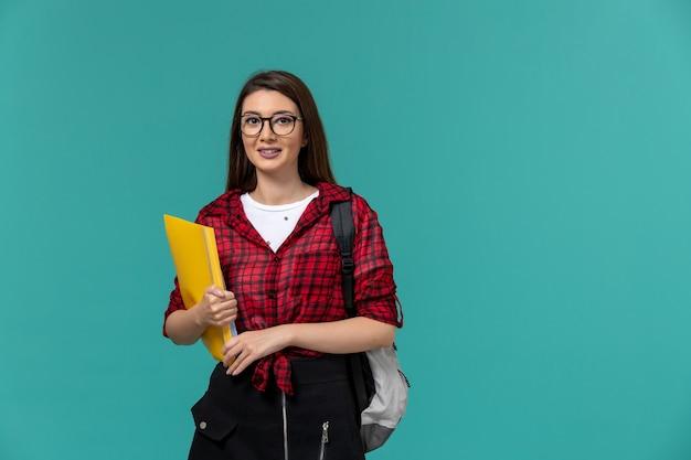Vue de face de l'étudiante portant sac à dos et tenant des fichiers sur le mur bleu