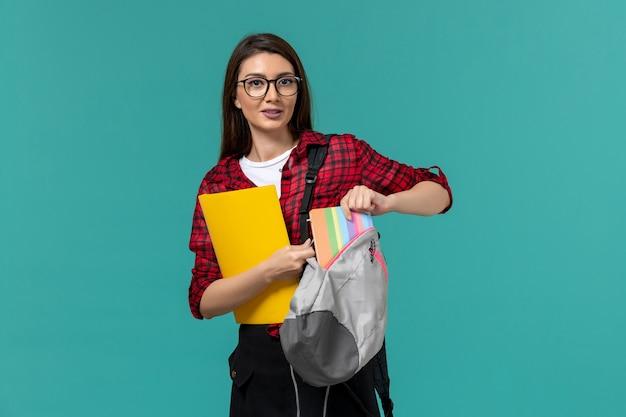 Vue de face de l'étudiante portant un sac à dos et tenant des fichiers prenant un cahier sur le mur bleu clair