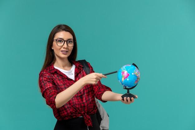 Vue de face de l'étudiante portant sac à dos tenant petit globe et stylo sur mur bleu clair