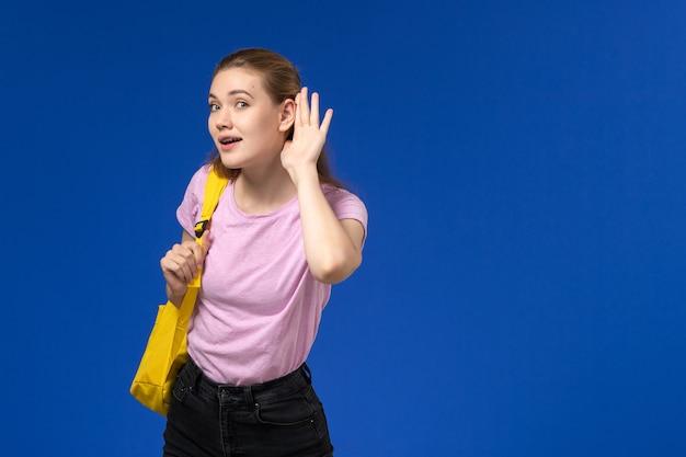 Vue de face de l'étudiante en t-shirt rose avec sac à dos jaune essayant d'entendre sur le mur bleu