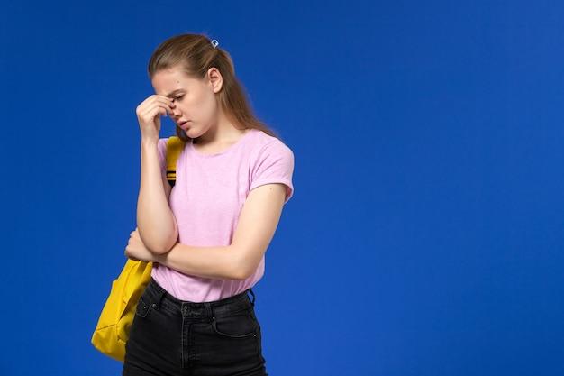 Vue de face de l'étudiante en t-shirt rose avec sac à dos jaune fille déprimée sur le mur bleu