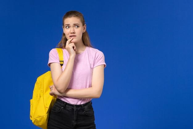 Vue de face de l'étudiante en t-shirt rose avec sac à dos jaune pensant sur le mur bleu