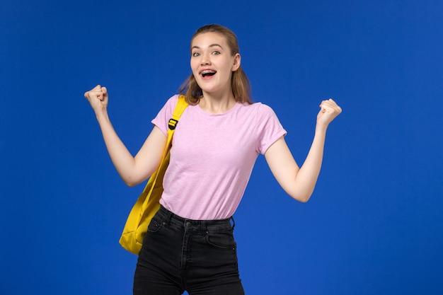 Vue de face de l'étudiante en t-shirt rose avec sac à dos jaune se réjouissant sur mur bleu clair