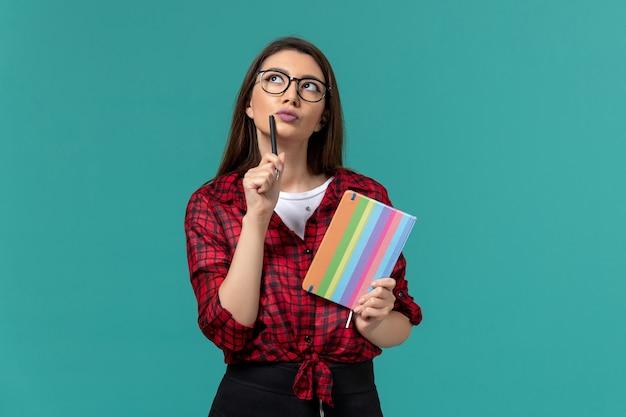 Vue de face de l'étudiante tenant un cahier et un stylo pensant sur le mur bleu clair