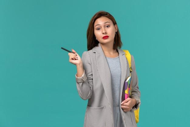 Vue de face de l'étudiante en veste grise portant un sac à dos jaune tenant un cahier avec un stylo sur le mur bleu