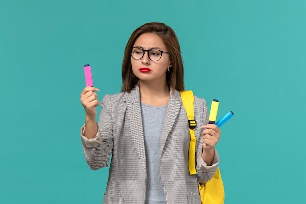 Vue de face de l'étudiante en veste grise portant son sac à dos jaune tenant des feutres sur le mur bleu clair