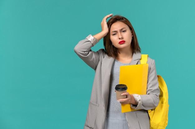 Vue de face de l'étudiante en veste grise portant son sac à dos jaune tenant des fichiers et du café sur le mur bleu
