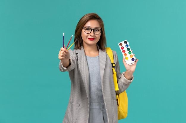 Vue de face de l'étudiante en veste grise portant son sac à dos jaune tenant des peintures sur le mur bleu