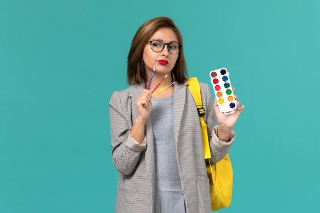 Vue de face de l'étudiante en veste grise portant son sac à dos jaune tenant des peintures pensant sur le mur bleu