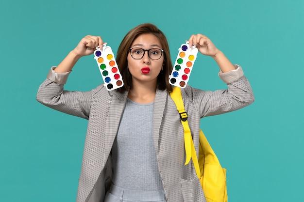 Vue de face de l'étudiante en veste grise portant son sac à dos jaune tenant des peintures pour dessiner sur le mur bleu