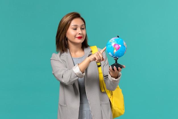 Vue de face de l'étudiante en veste grise portant son sac à dos jaune tenant petit globe sur mur bleu clair