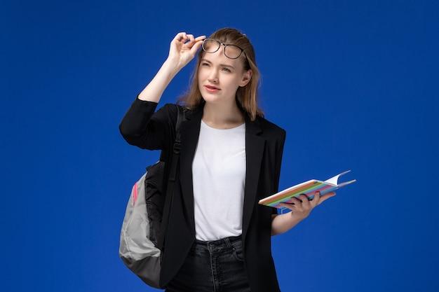 Vue de face étudiante en veste noire portant sac à dos tenant un cahier sur le mur bleu livres de leçon école collège université