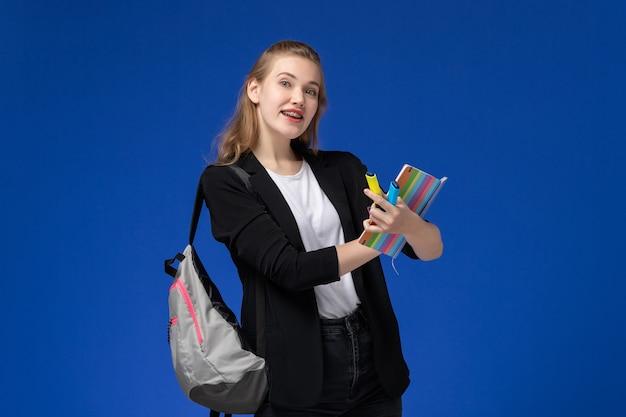 Vue de face étudiante en veste noire portant sac à dos tenant des feutres et un cahier sur le mur bleu leçon école collège université