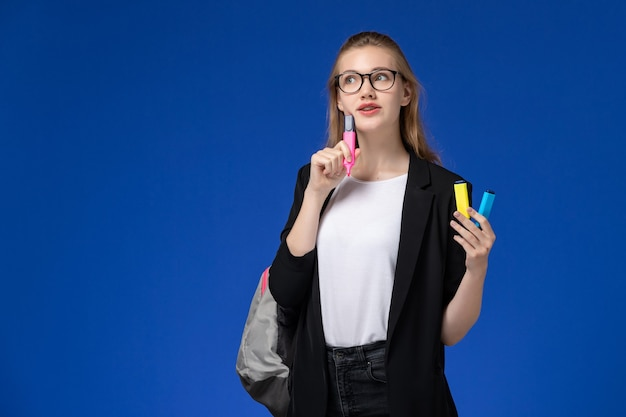 Vue de face étudiante en veste noire portant sac à dos tenant des feutres pensant sur le mur bleu leçons école college college