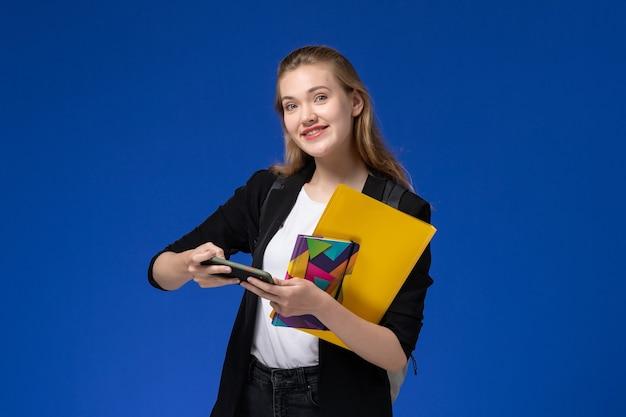 Vue de face étudiante en veste noire portant un sac à dos tenant un fichier et un cahier à l'aide de téléphone sur le mur bleu clair des leçons d'université du collège