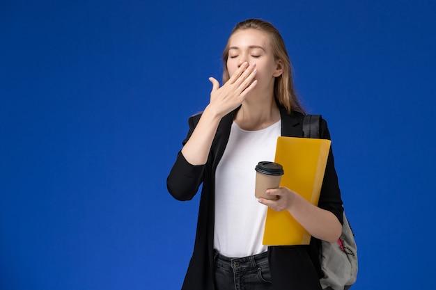Vue de face étudiante en veste noire portant sac à dos tenant le fichier jaune et le café bâillant sur le mur bleu école college college leçon