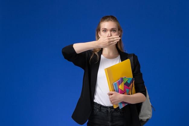Vue de face étudiante en veste noire portant sac à dos tenant des fichiers avec des cahiers sur le mur bleu clair leçon de l'université college