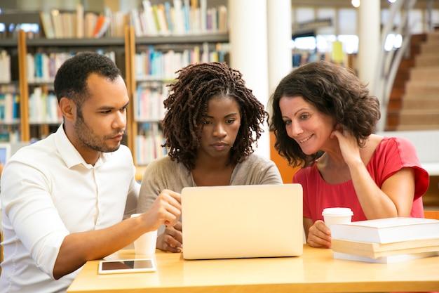Vue de face d'étudiants adultes fatigués à la recherche d'un ordinateur portable