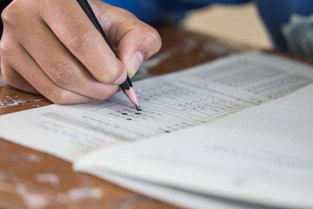 Vue de face étudiants asiatiques, titulaire d'un baccalauréat en écriture sur des quiz à choix multiples