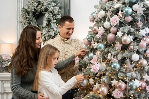 Vue de face de la famille et de l'arbre de noël