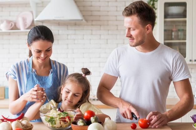 Vue de face famille heureuse cuisiner ensemble