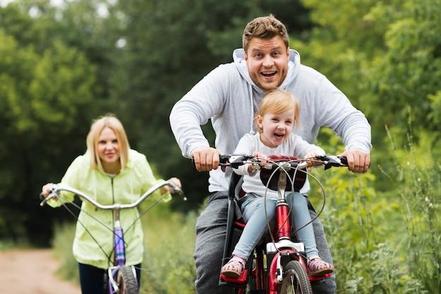 Vue de face famille heureuse avec des vélos