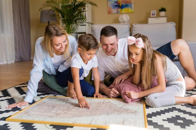 Vue de face de la famille à l'intérieur en regardant un imprimé bleu