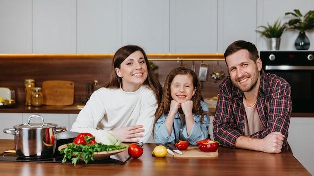 Vue de face de la famille posant dans la cuisine