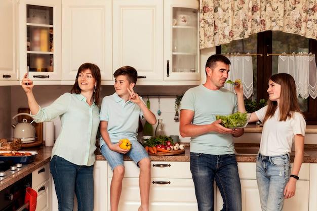 Vue de face de la famille posant avec de la nourriture dans la cuisine