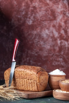 Vue de face de la farine de tranches de pain noir dans un bol sur une planche de bois et des pointes de couteaux de blé d'avoine cru sur fond de couleurs mélangées en détresse