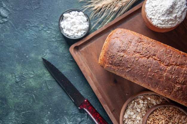 Vue de face de la farine de tranches de pain noir dans un bol sur une planche de bois et des pointes de couteaux de blé d'avoine crue sur le côté gauche sur fond de couleurs mélangées en détresse