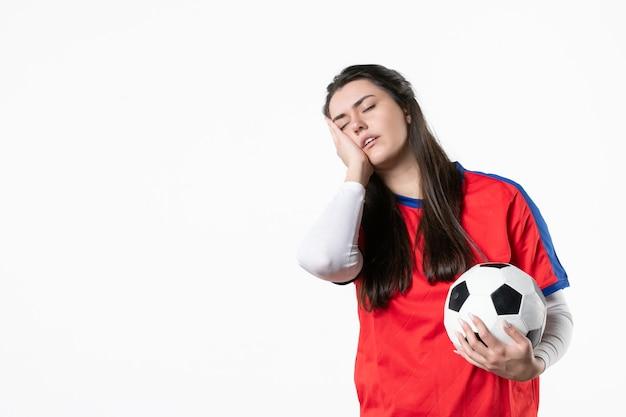 Vue de face fatiguée jeune femme en vêtements de sport avec ballon de foot