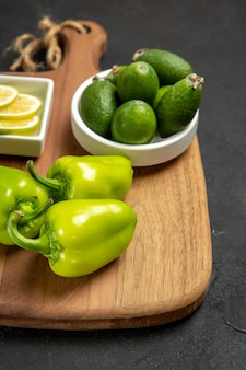 Vue de face feijoa frais avec poivron vert et citron sur surface sombre plante de repas d'agrumes santé fruits