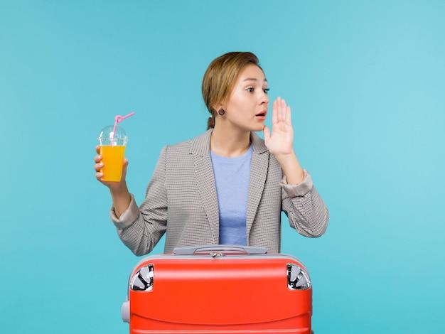 Vue de face femelle en vacances avec grand sac rouge tenant du jus de fruits frais sur fond bleu mer vacances avion voyage voyage voyage