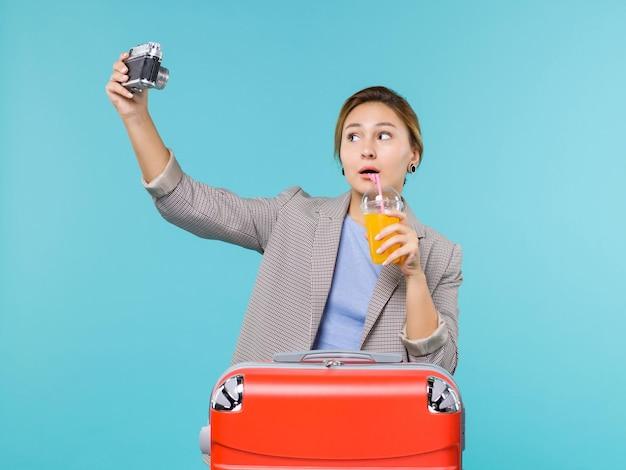Vue de face femelle en vacances tenant des jus de fruits frais et appareil photo prenant des photos sur fond b lue mer vacances voyage voyage voyage