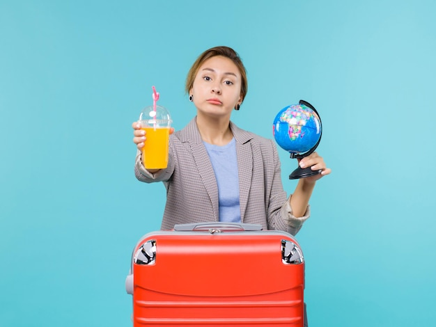 Vue de face femelle en vacances tenant des jus de fruits frais et globe sur fond bleu clair voyage en mer vacances voyage voyage