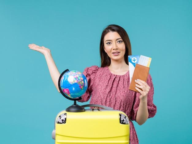 Vue de face femelle en voyage tenant son billet sur le bureau bleu voyage en mer femme voyage vacances voyage