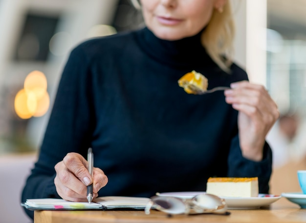 Vue de face d'une femme d'affaires âgée travaillant tout en ayant un dessert