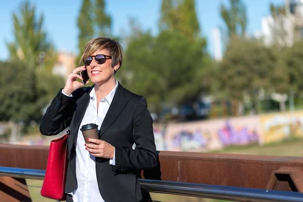 Vue de face d'une femme d'affaires élégante et souriante, lunettes de soleil