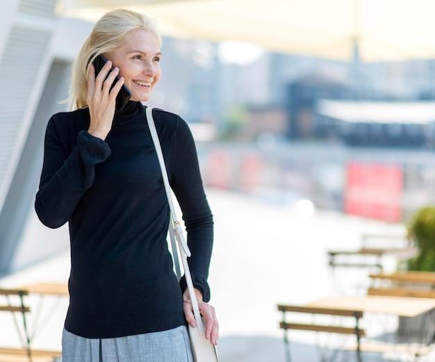 Vue de face de la femme d'affaires plus âgée smiley sur un appel téléphonique à l'extérieur