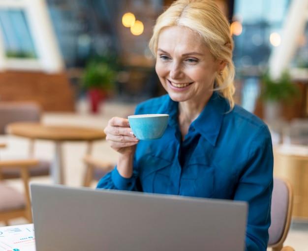 Vue de face de la femme d'affaires plus âgée smiley ayant une tasse de café et travaillant sur ordinateur portable