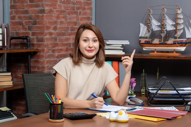 Vue de face d'une femme d'affaires souriante pointant le doigt vers le haut assis au mur