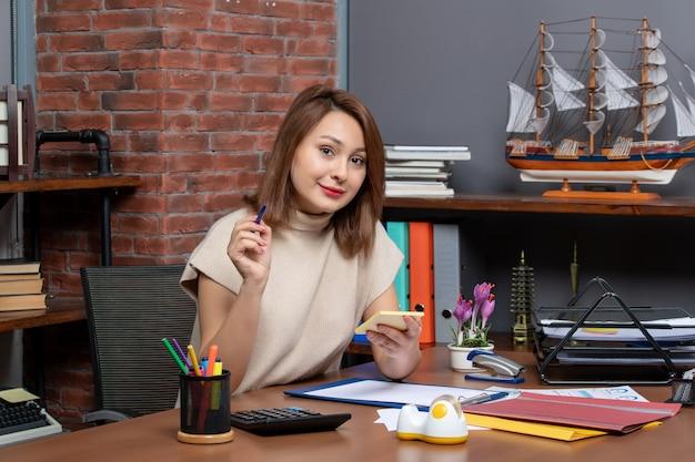 Vue de face d'une femme d'affaires souriante tenant un stylo et des papiers assis au mur
