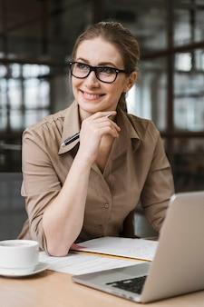 Vue de face de la femme d'affaires travaillant avec un ordinateur portable au bureau