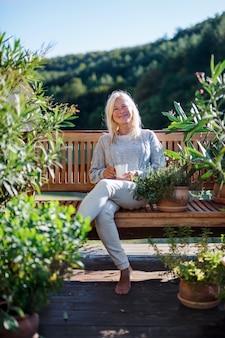 Vue de face d'une femme âgée avec un café assis à l'extérieur sur une terrasse, au repos.