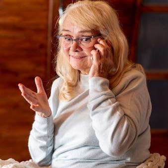 Vue de face d'une femme âgée parlant au téléphone