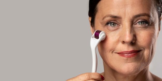 Vue de face de la femme âgée smiley à l'aide de rouleau de visage sur sa peau avec copie espace