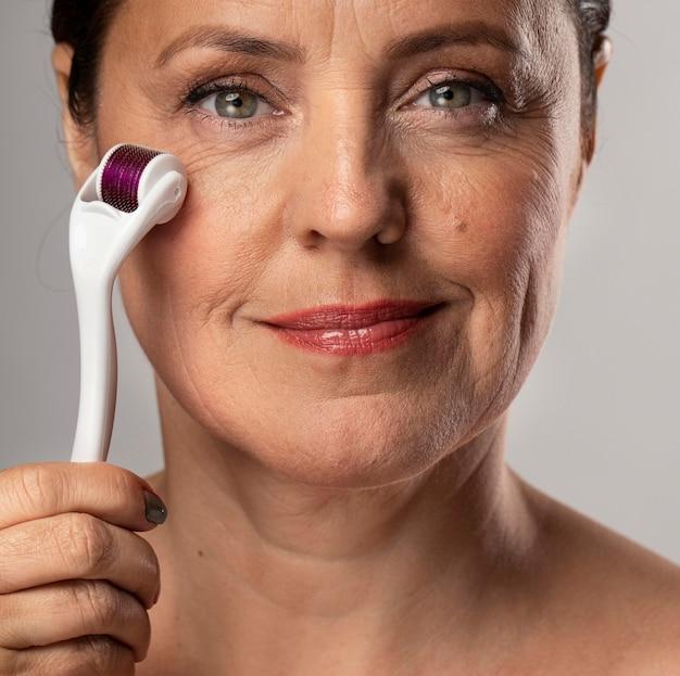 Vue de face de la femme âgée smiley à l'aide de rouleau de visage sur sa peau